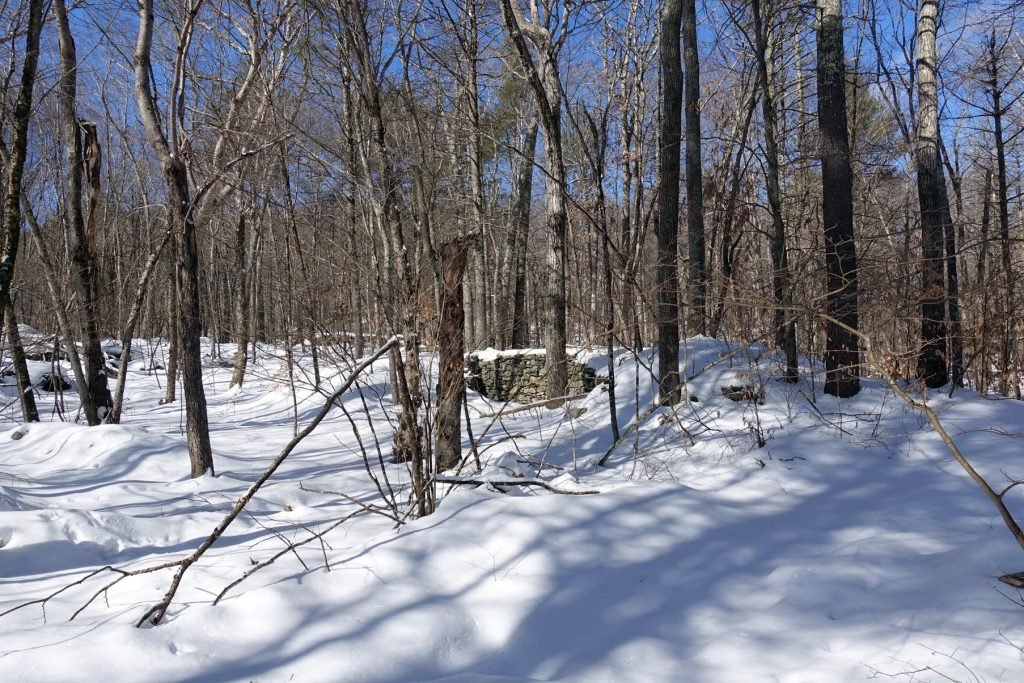 a ruined stone foundation in the snow